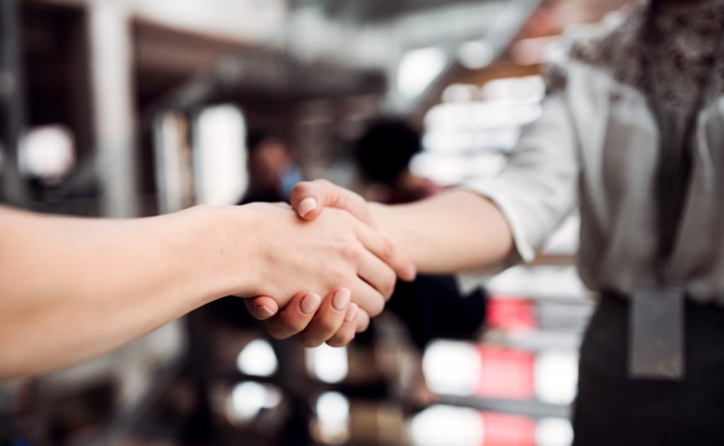 A midsection of young businesswomen, shaking hands.